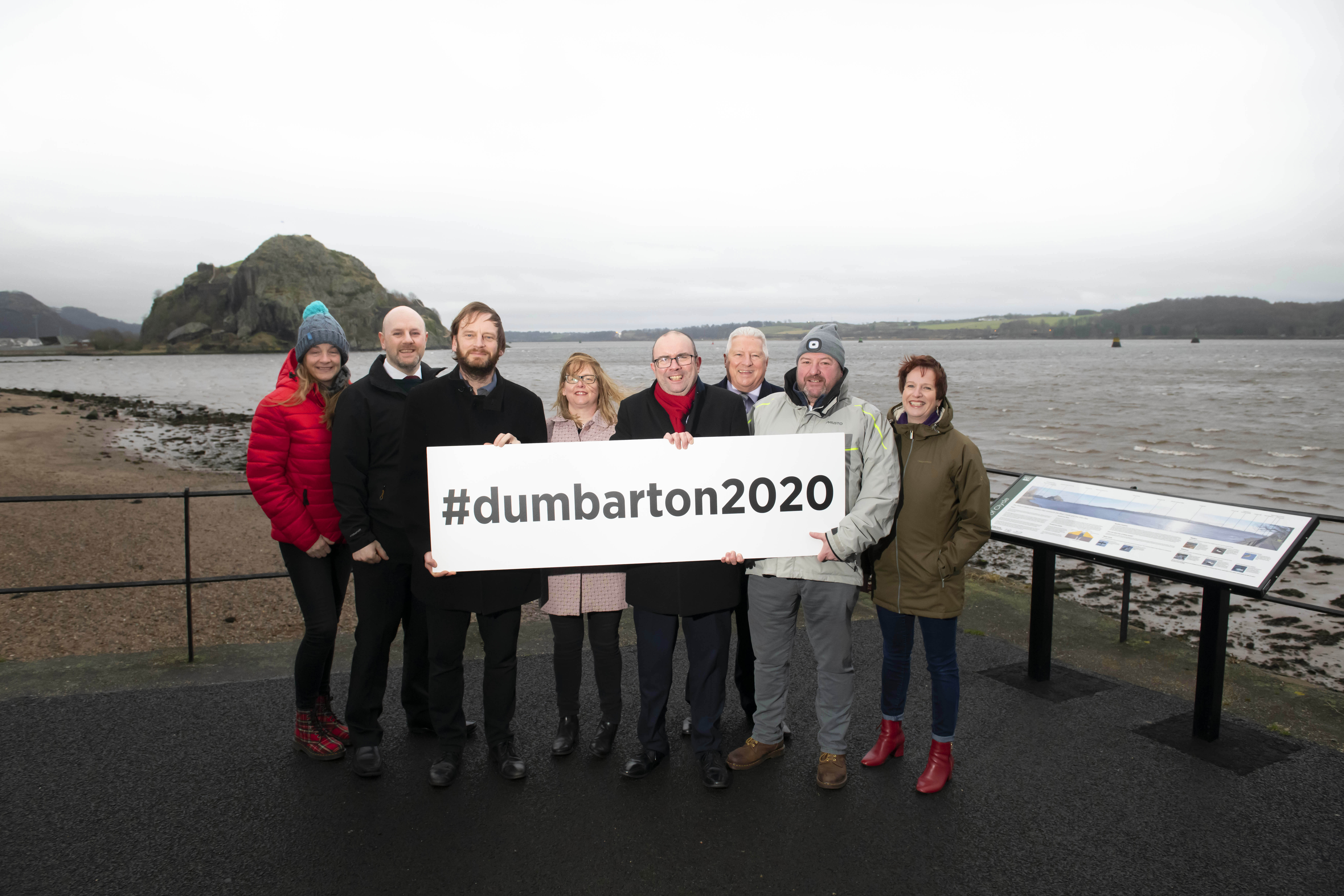 Standing at the shoreline to advertise Dumbarton Festival, holding a sign -  #dunbarton2020