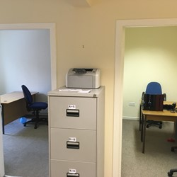 Filing cabinet in between 2 doors leading into offices