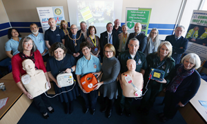 Heart start defibrillator launch group photo - 20 people with defibrillator equipment